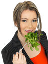 Young business woman eating mixed leaves salad a dslr royalty free image of an attractive with dark blonde hair a leaf looking Royalty Free Stock Images