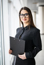 Young business woman with a folder against office windows Royalty Free Stock Photo