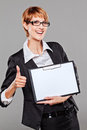 Young business woman gesturing thumb up and holding a clipboard on grey Stock Photography