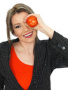 Young business woman holding a raw tomato over her eye dslr royalty free image of attractive mucking about large red to promote Stock Photo