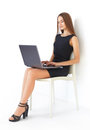 Young business woman with laptop beautiful sitting on chair working on white background Royalty Free Stock Photography