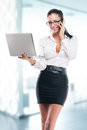 Young business woman with laptop and mobile on office background Royalty Free Stock Photos