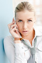 Young business woman looking at camera speaking beautiful talking on mobile phone office window Stock Image