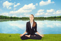 Young business woman meditating sitting in lotus pose on grass on bank of lake Royalty Free Stock Photography