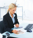 Young business woman sitting at office desk Stock Image