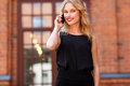 Young business woman talking on mobile phone and smiling widely Royalty Free Stock Photo