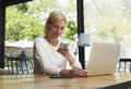 Young business woman type text oh cell phone while work with laptop computer in loft Royalty Free Stock Photo