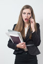 Young business woman is upset speaking on the phone with a professional outfit angry while carry a bunch of items like a computer Stock Photo