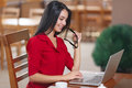 Young business woman uses laptop in cafe Royalty Free Stock Photo
