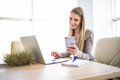 Young business woman using phone in hand with laptop at office Royalty Free Stock Photo