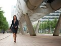 Young business woman walking on sidewalk portrait of a Royalty Free Stock Image
