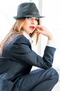 Young business woman wearing man s suit hat in office looking bossy stylish Stock Photo