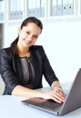 Young business woman working on a laptop portrait of beautiful brunette in office Royalty Free Stock Photography