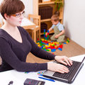 Young business woman working women on a laptop with her child playing at the back Royalty Free Stock Photos