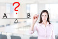 Young business woman writing A and B compare on balance bar. Office background. Royalty Free Stock Photo