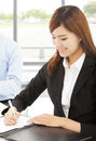 Young business woman writing document with colleague women in office Stock Photography