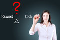 Young business woman writing question with risk compare to reward on balance bar. Blue background.