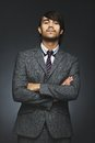 Young businessman with attitude portrait of business person looking at you an arms crossed on black background mixed race Royalty Free Stock Photo