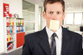 Young businessman with blank note on his mouth inside office Stock Photo