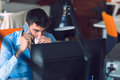 Young businessman busy working on laptop computer while talking on the smart-phone at office. Royalty Free Stock Photo