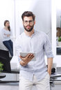 Young businessman with digital tablet portrait of holding in his hands while looking at camera and smiling business team working Royalty Free Stock Photography