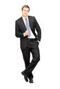 Young businessman in formalwear leaning against wall full length portrait of a isolated on white background Stock Photo