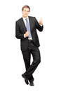 Young businessman in formalwear leaning against wall and giving full length portrait of a thumb up isolated on white background Stock Photo
