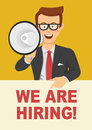 Young businessman with glasses speaking with megaphone pointing to blank board with we are hiring text