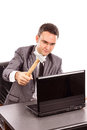 Young businessman with a hammer ready to smash his laptop while sitting at office desk isolated on white Stock Photos