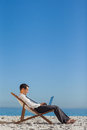 Young businessman on his deck chair using his laptop the beach Royalty Free Stock Photo