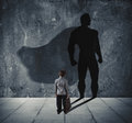 Young businessman with his shadow of super hero on the wall. Concept of powerful small man Royalty Free Stock Photo