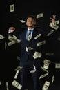 Young businessman holding baseball bat and dollar banknotes falling on black Royalty Free Stock Photo