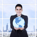 Young businessman holding a globe at modern office Royalty Free Stock Photo