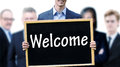 Young businessman holding up a chalkboard with word Welcome Royalty Free Stock Photo