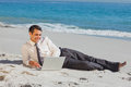 Young businessman lying on the sand using his laptop relaxing Royalty Free Stock Photo