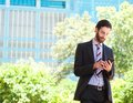 Young businessman reading text message on mobile phone portrait of a Stock Photo