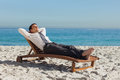 Young businessman relaxing on a deck chair the beach Stock Images
