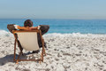 Young businessman relaxing on his sun lounger the beach Royalty Free Stock Photo