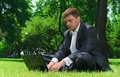 Young businessman resting in a park on the grass successful looking at latest news internet Royalty Free Stock Images