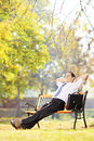 Young businessman seated on a bench relaxing in a park wooden Royalty Free Stock Images