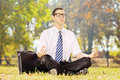 Young businessman seated on a green grass meditating in a park sunny day Stock Photography