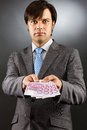 Young businessman showing euro banknotes over gray background Royalty Free Stock Image