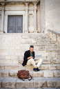 Young businessman sitting on steps of city building and using his phone Royalty Free Stock Photo