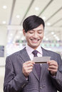Young businessman smiling and looking down at airplane ticket at the airport beijing Royalty Free Stock Image