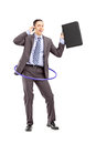 Young businessman in suit dancing with hula hoop and talking on full length portrait of a a a mobile phone isolated white Royalty Free Stock Photography