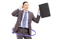 Young businessman in suit dancing with a hula hoop and talking o on mobile phone isolated on white background Stock Photos