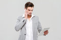 Young businessman talking on cellphone and using tablet handsome Royalty Free Stock Images