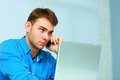 Young businessman talking on the phone and looking at copyspace in office Stock Photography