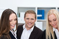 Young businessman with two female coworkers handsome flanked by smiling at the camera Stock Photos