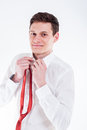 Young businessman tying a red tie and smiling close up of Stock Photography